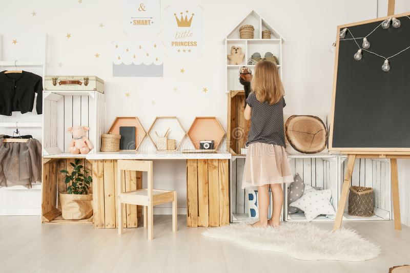 Little girl organizing her toys in white Nordic style bedroom in stock images