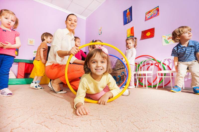 Little girl and other kids crawl though hoops. Little girl and other kids boys and girls crawl though hoops with teacher holding tunnel stock photo
