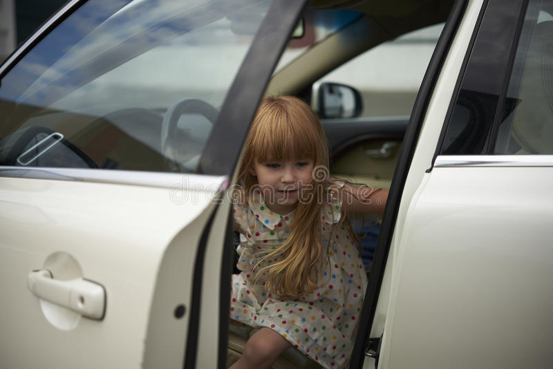 Little girl out of the white car stock photo