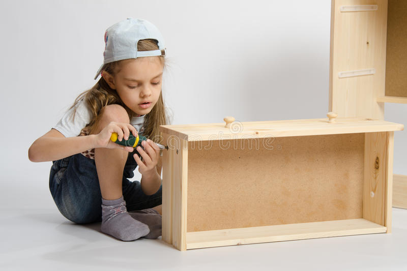 Little girl in overalls collector of furniture making box on the dresser royalty free stock image