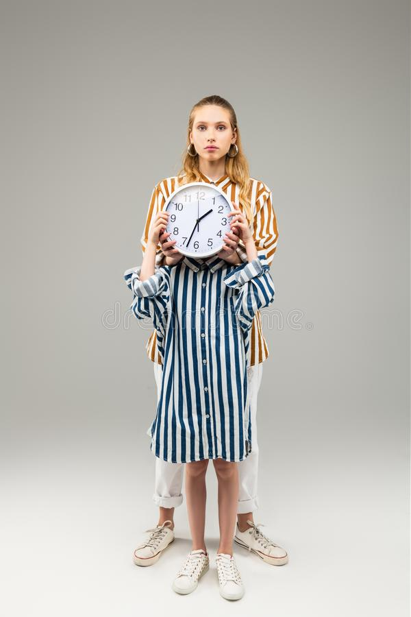 Little girl in oversize striped shirt closing her face with round clock royalty free stock photos