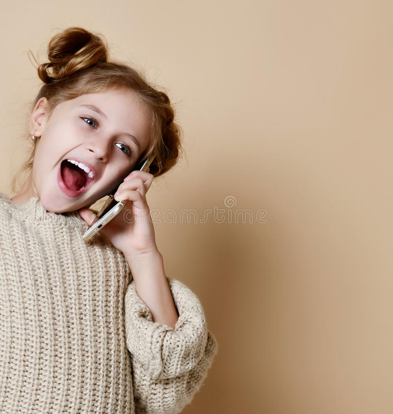 Little girl speaking by cell phone, nude background royalty free stock photography