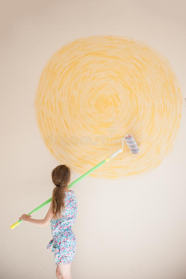 Talented little girl with paint roller on the background of wall with yellow sun painted royalty free stock image