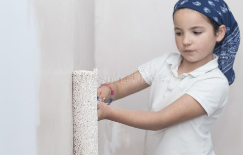 Little girl with paint roller in hand. Kids Helping House Chores concept royalty free stock photos