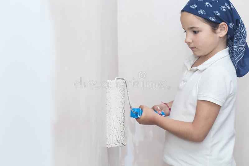 Little girl with paint roller in hand. Kids Helping House Chores concept stock photos