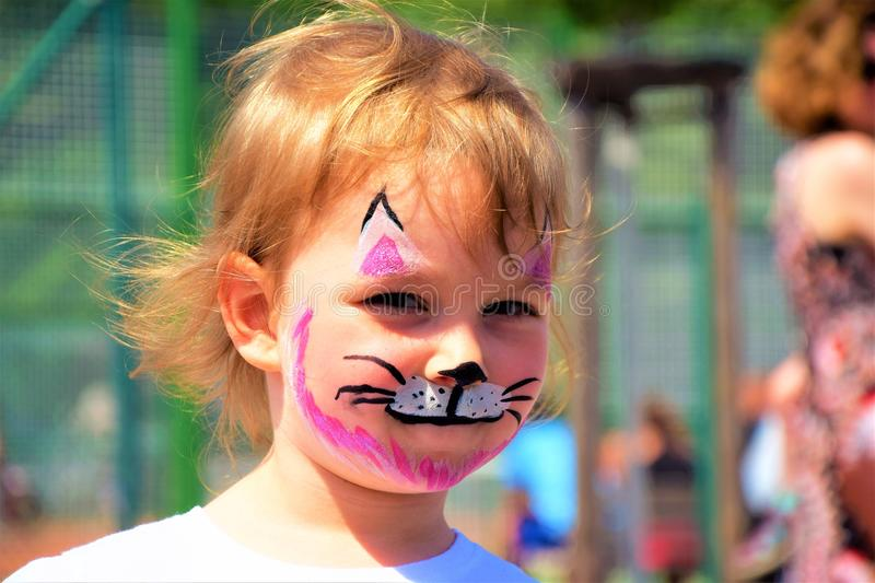 A little girl painted like a kitten stock photography