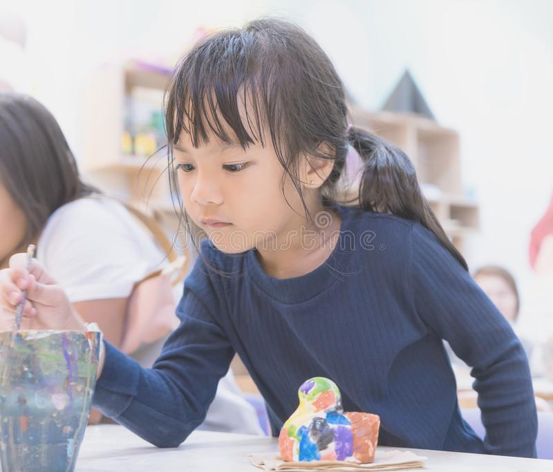 Little girl painting in art classroom stock photos