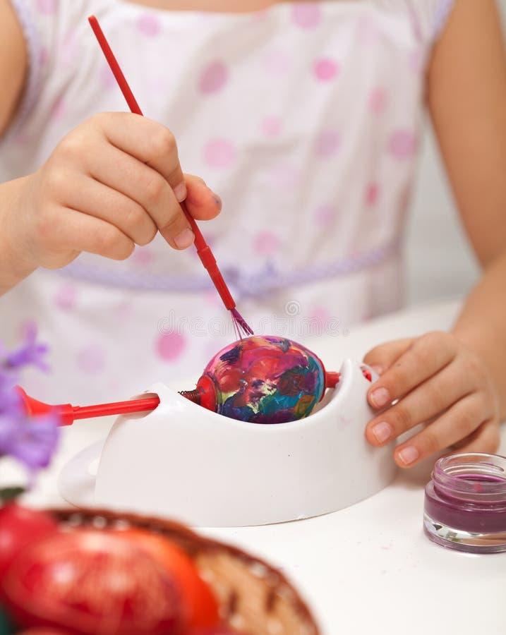 Little girl painting easter eggs stock images