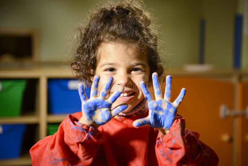 Little girl painting with hands in kindergarten stock photo
