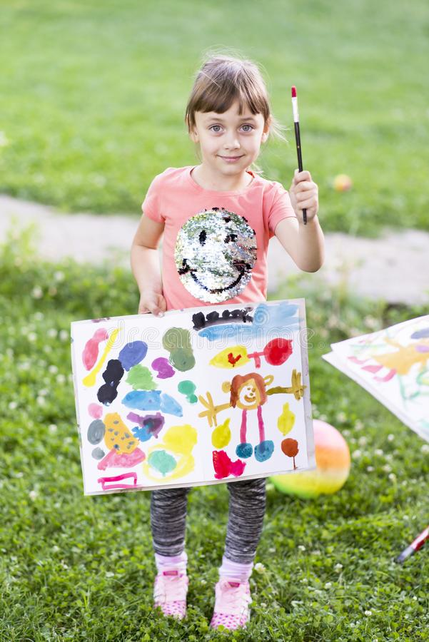 Little girl painting with paintbrush and colorful paints stock photography