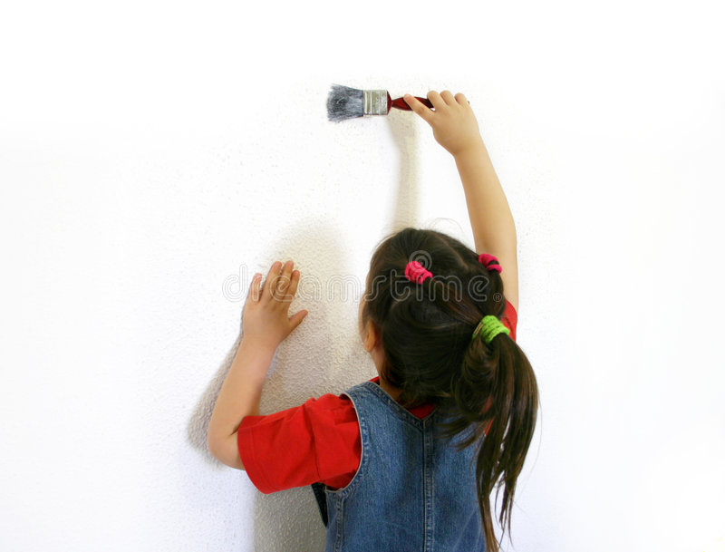 Little girl painting a wall stock images