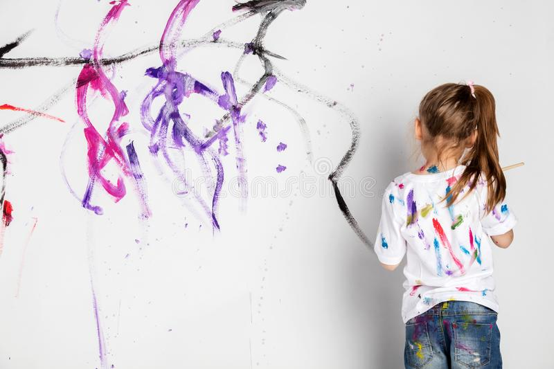 Little girl painting a white wall with colorful paint. Messy fun. Child`s creativity development stock image