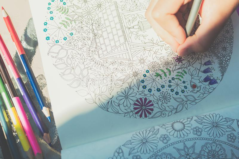 Little girl paints a coloring book royalty free stock image