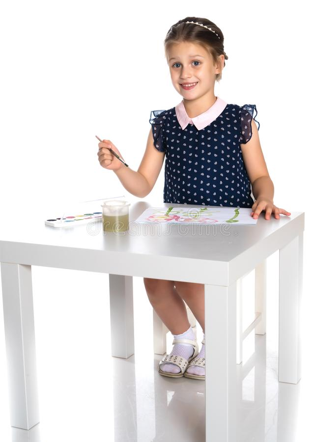 A little girl paints with paint and brush. stock image