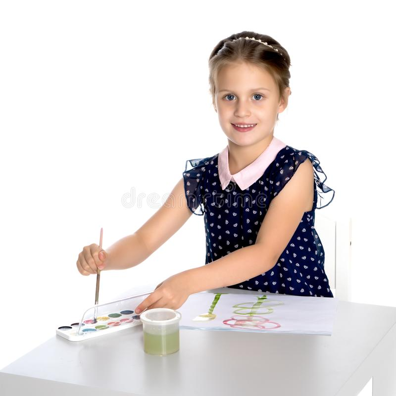 A little girl paints with paint and brush. royalty free stock photo