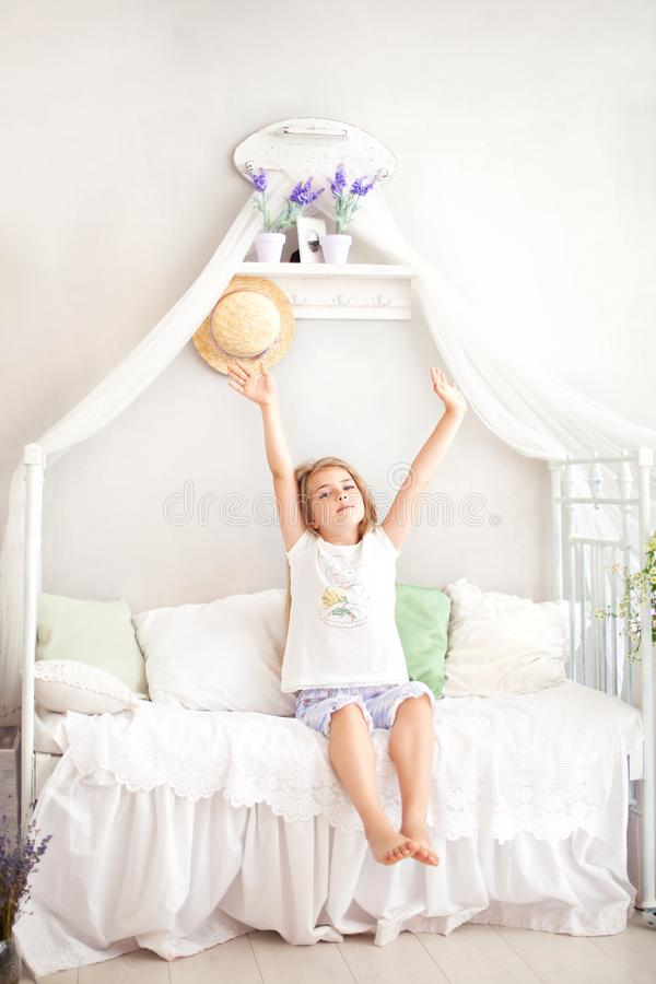 A little girl in pajamas enjoys a sunny morning and stretches herself in bed. Good morning at home. The child wakes up from a drea royalty free stock photos