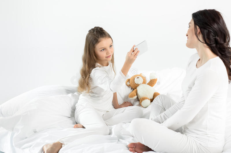 Little girl in pajamas photographing mother sitting on bed stock photos