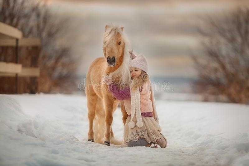 Little girl with palomino pony in winter park royalty free stock image