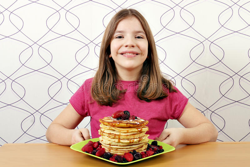 Little girl with pancakes. Happy little girl with pancakes royalty free stock images