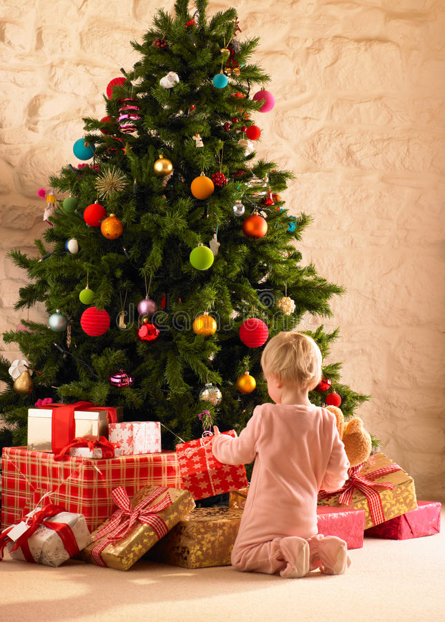 Little girl with parcels round Christmas tree stock image