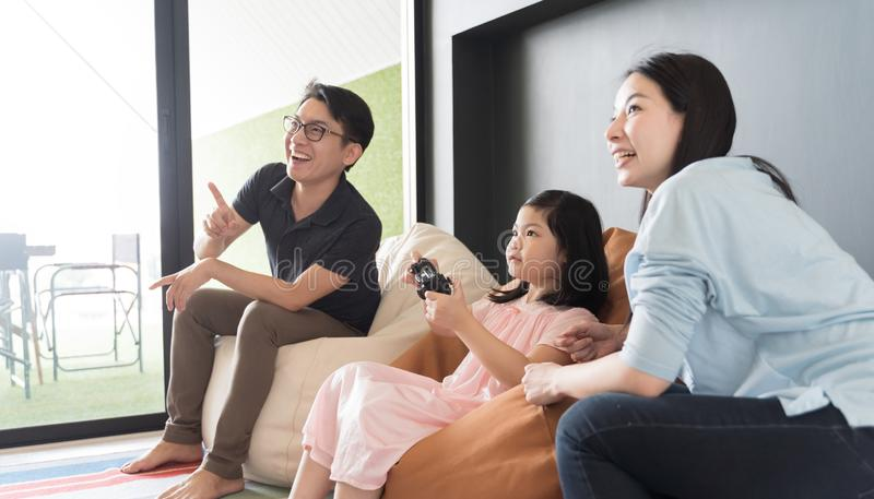 Little girl and parent family playing video game at home. royalty free stock photos