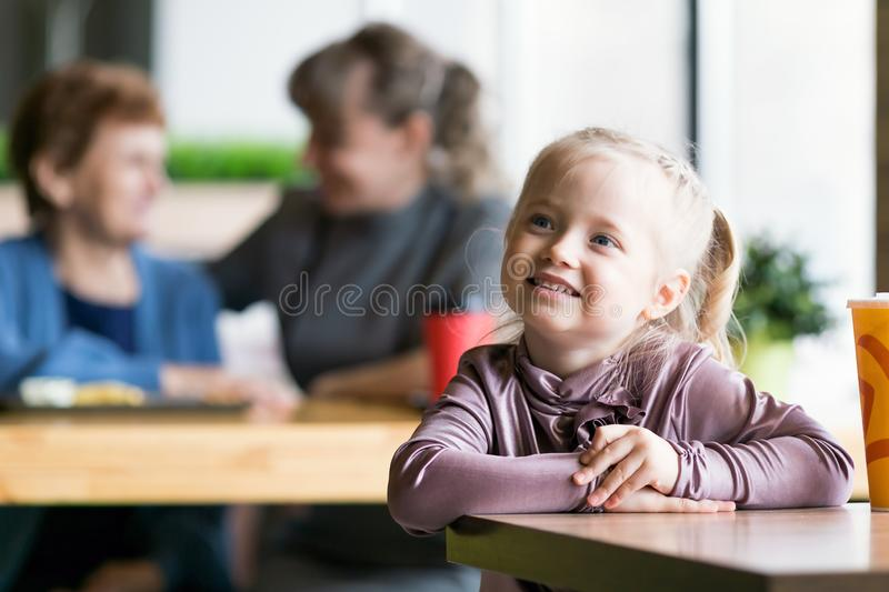 A little girl without parental supervision. Child was left alone in the cafe while mother and grandmother were talking to each other stock photo