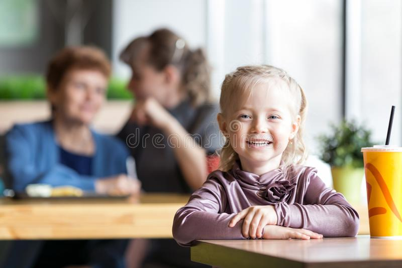 A little girl without parental supervision. The child was left alone in the cafe while mother and grandmother were talking to each other royalty free stock photo