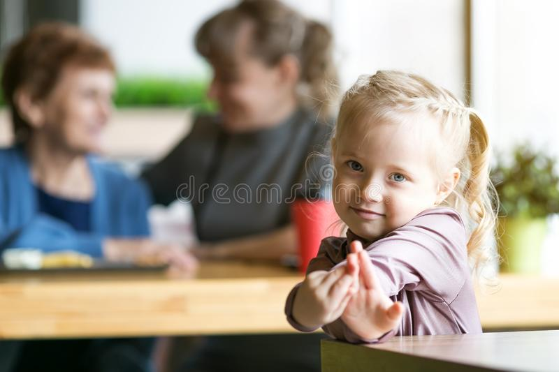 A little girl without parental supervision. The child was left alone in cafe while mother and grandmother were talking to each other royalty free stock image