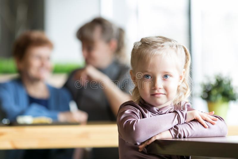A little girl without parental supervision. The child was left alone in the cafe while mother and grandmother were talking to each other stock image