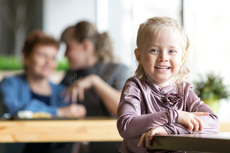 A little girl without parental supervision. The child was left alone in the cafe while mother and grandmother were talking to each other royalty free stock photography