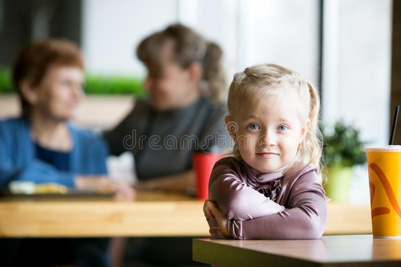 A little girl without parental supervision. The child was left alone in the cafe while mother  grandmother were talking to each other stock photos