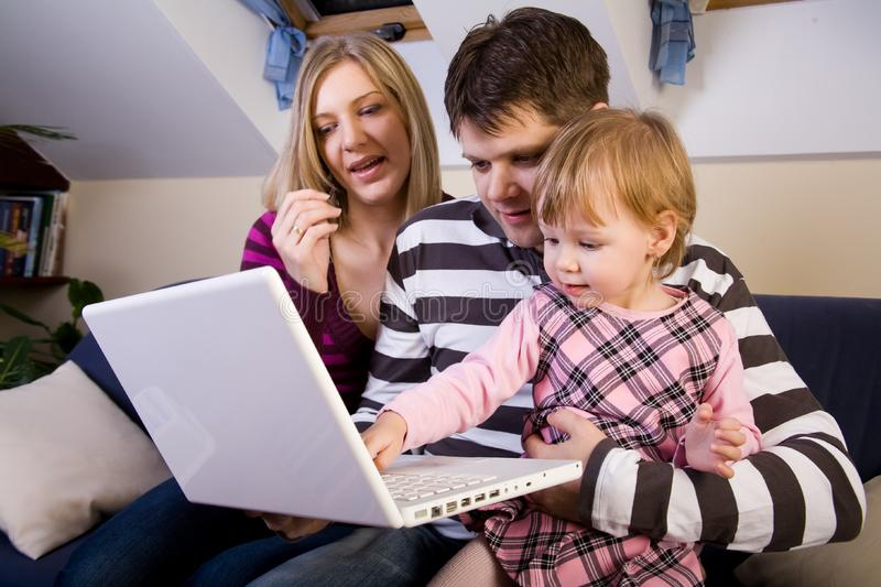 Little girl with parents play with a laptop stock photography