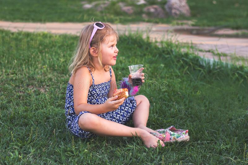 Little girl in the park, sitting on the grass barefoot and eating pizza royalty free stock images