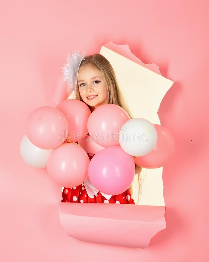 Little girl in party dress looking at camera with her pink balloon. royalty free stock photo