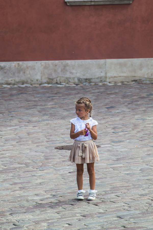 Thoughtful little girl standing alone on the pavement in the square. Little girl   on the pavement in the , baby, old, , stone, city, child, kid, dark, big stock images