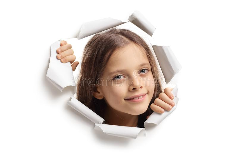 Little girl peeping through paper hole royalty free stock image