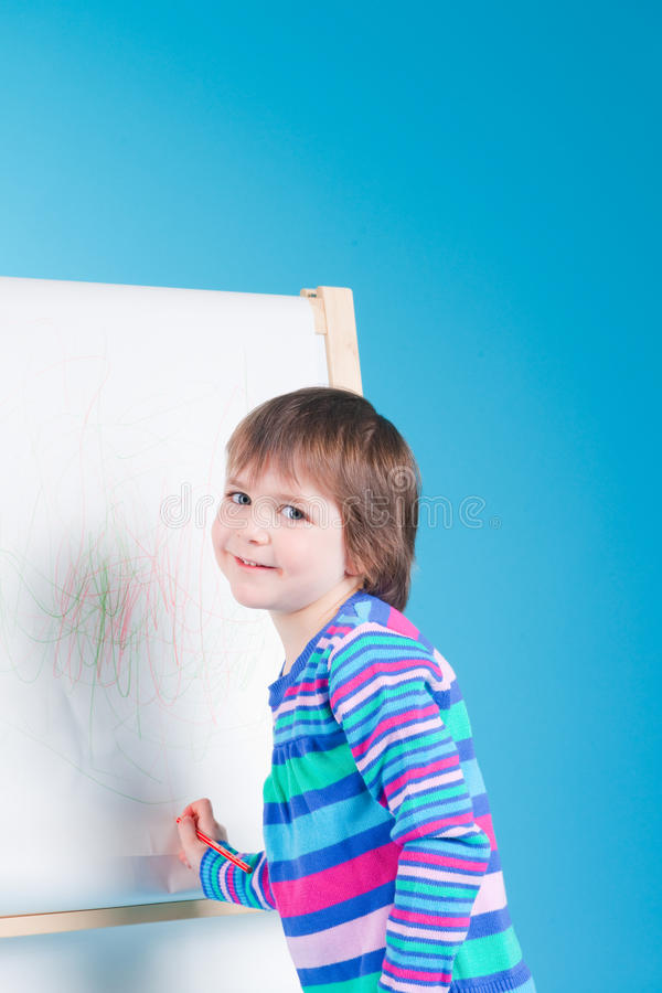 Download Little Girl With Pencil At Easel Stock Photo - Image: 13649840