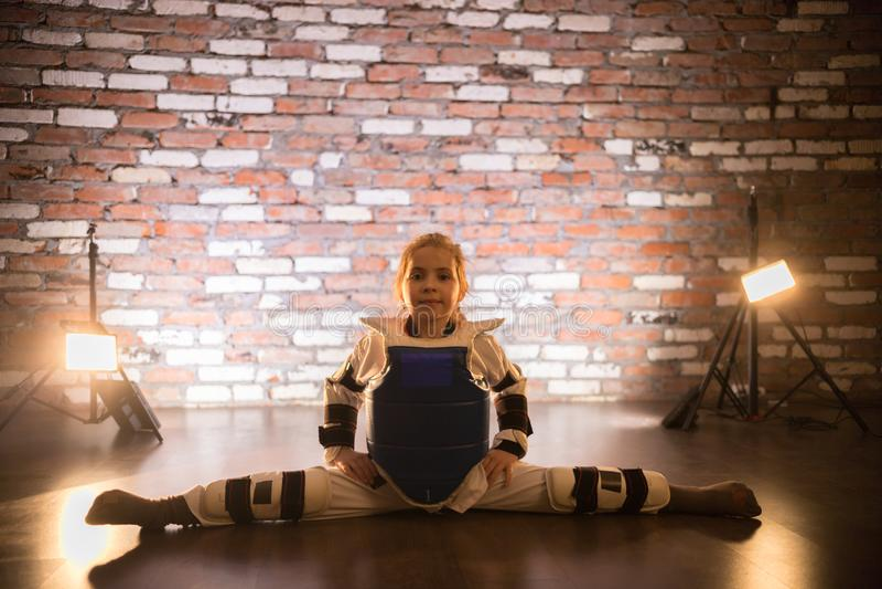 A little girl performing horizontal split in karate uniform stock photos
