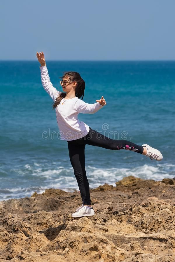 Little girl performs Arabesque on the rocks of the sea royalty free stock photography