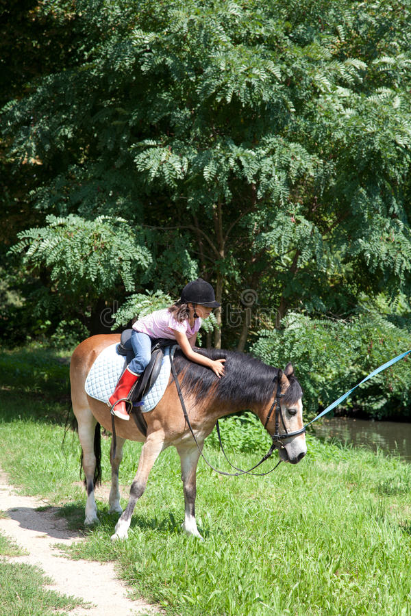 Little girl petting a horse while horseback riding royalty free stock images