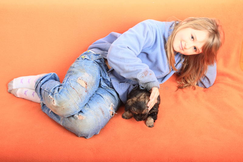 Little girl petting a puppy. Little kid - smiling blond girl in blue pullover and pants with holes lying on orange couch and petting brown puppy - dog royalty free stock images