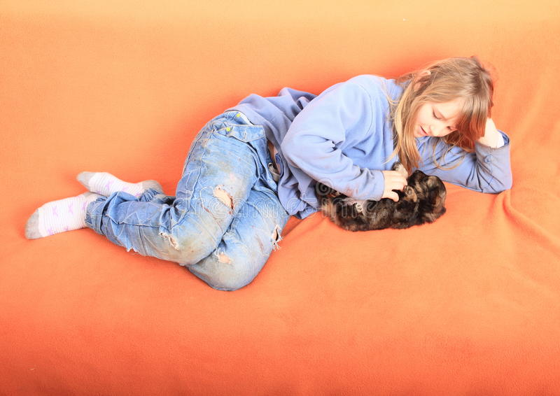 Little girl petting a puppy. Little kid - smiling blond girl in blue pullover and pants with holes lying on orange couch and petting brown puppy - dog stock photo