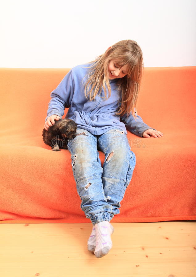 Little girl petting a puppy. Little kid - smiling blond girl in blue pullover and pants with holes sitting on orange couch and petting brown puppy - dog royalty free stock images