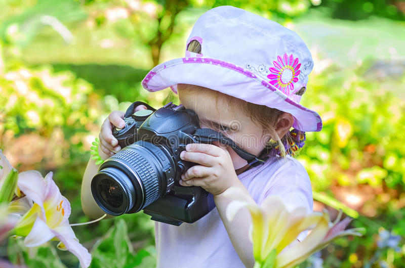Little girl photographing flowers stock images