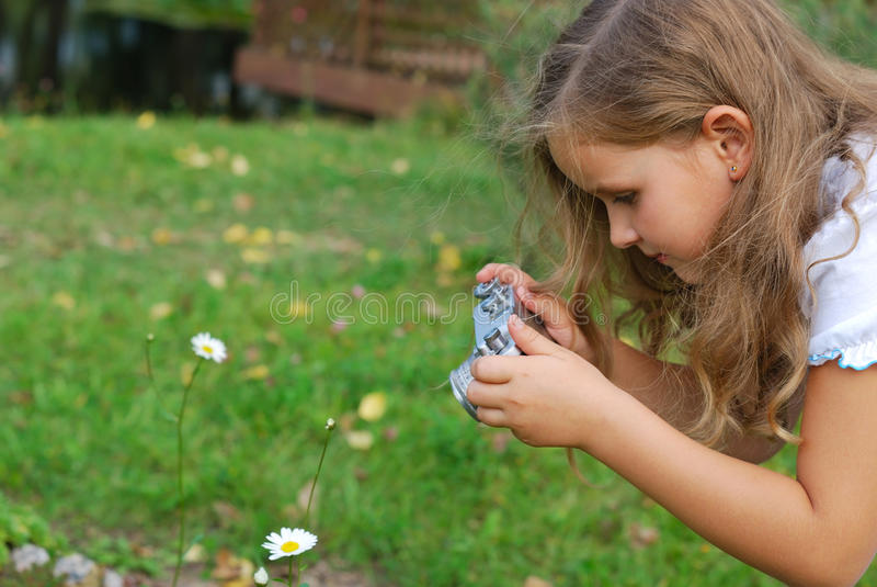The little girl photographs a flower royalty free stock images