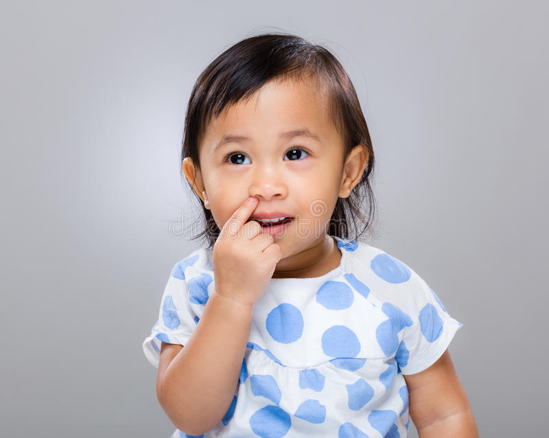 Little girl pick nose. With gray background stock photography