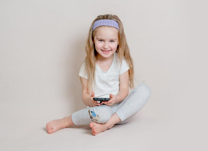 Little girl in pigamas sitting on the floor stock photo