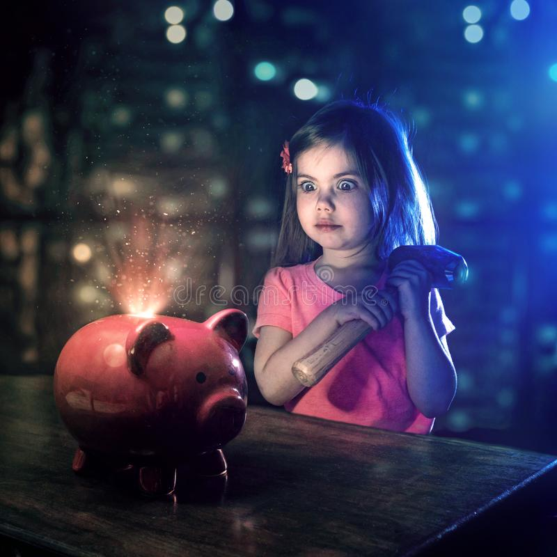 Little girl and piggy bank. A little girl looks at her piggy bank with a hammer in hand stock image