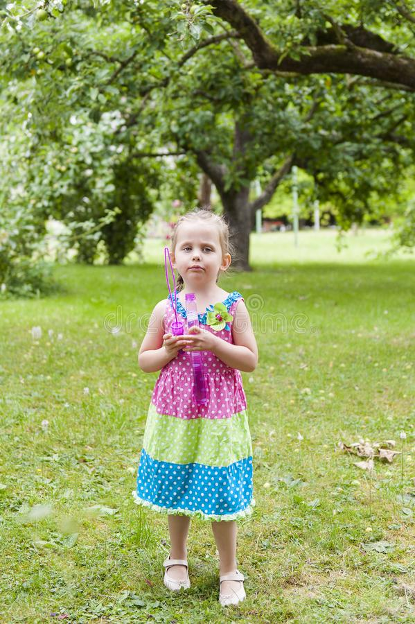 Little girl with pigtails in a colorful dress pensively standing in the park with soap bubbles royalty free stock photography