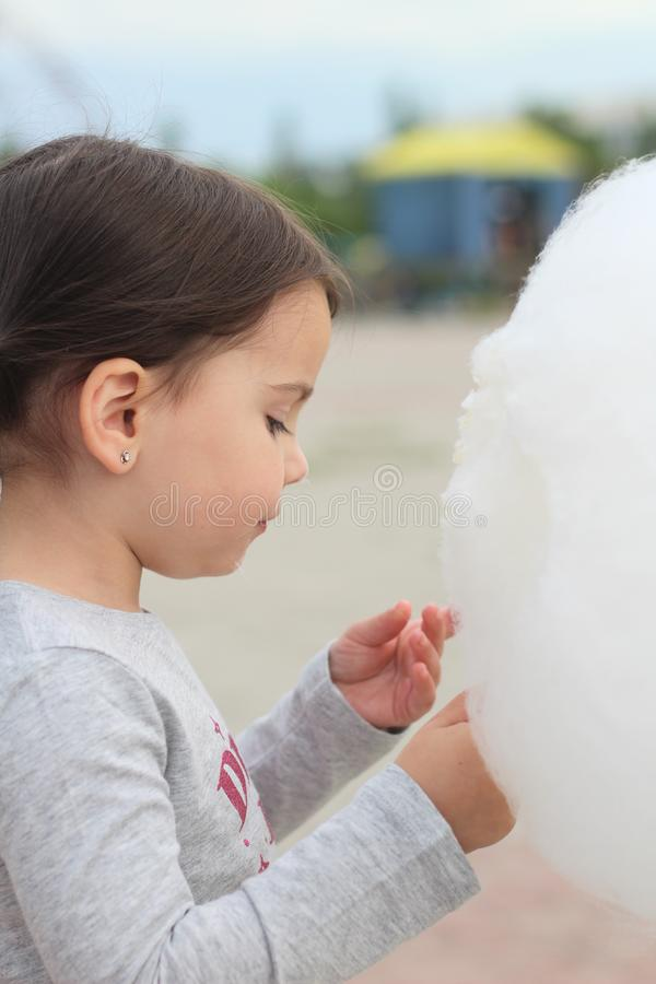 Little girl with pigtails holds in her hand a large ball of cotton candy at a city celebration stock photography